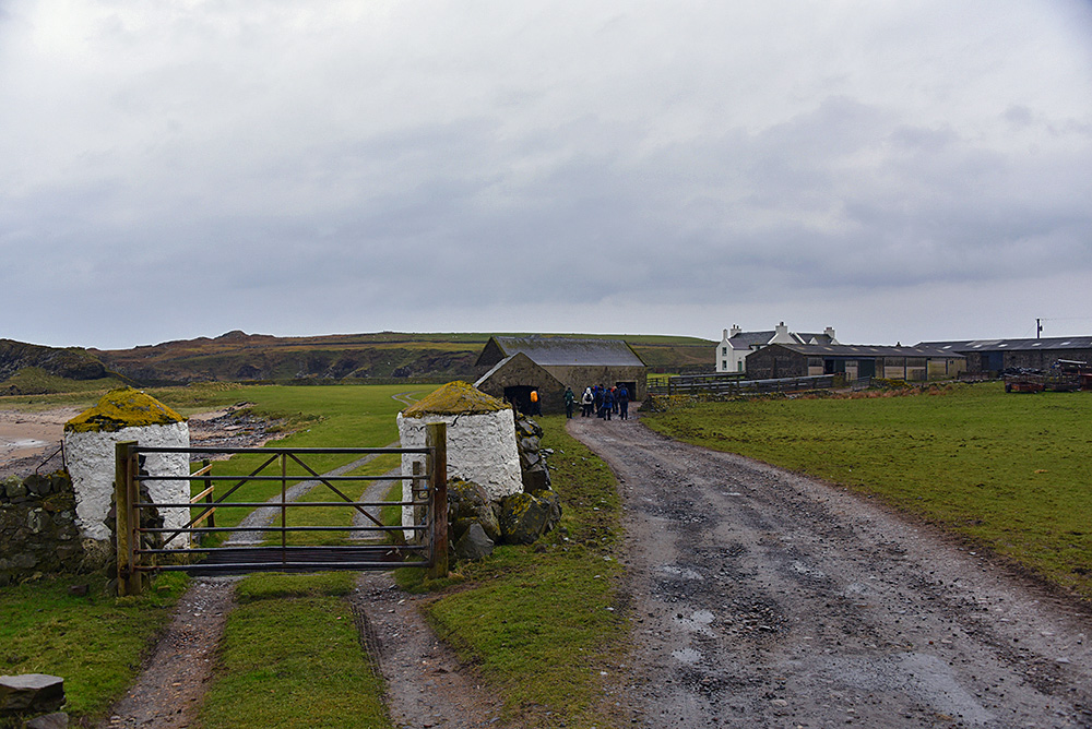 Picture of a remote farm on a dreich overcast day, a group of walkers on the track to the farm