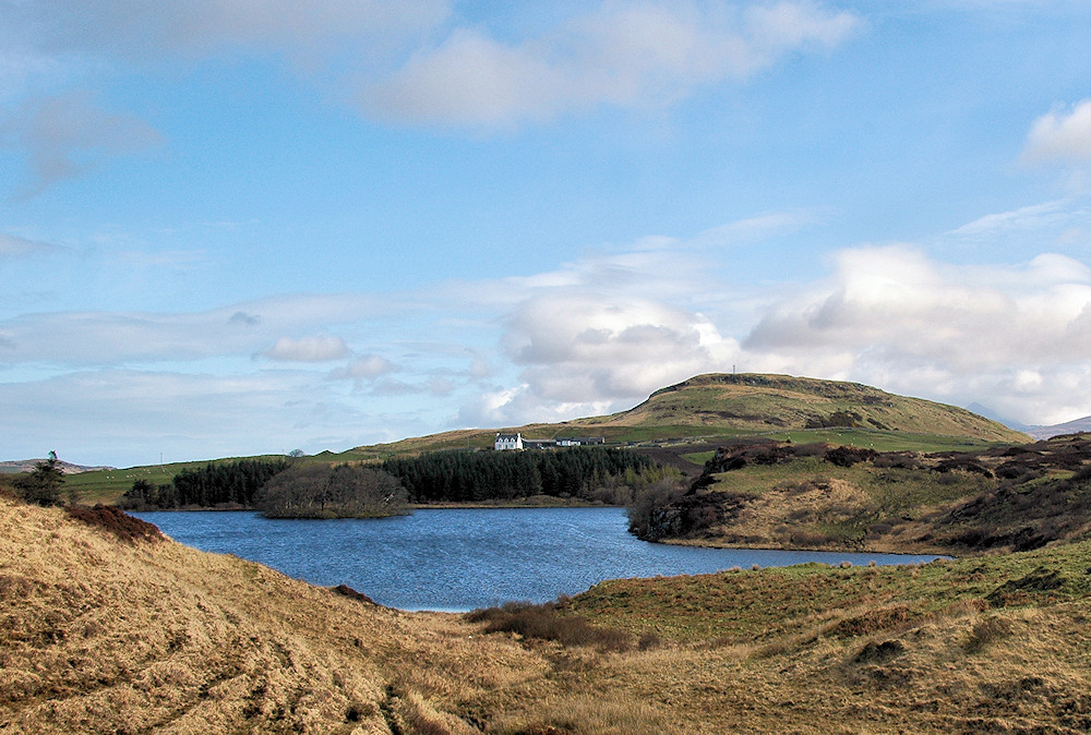 Picture of a loch (lake) with a small island, a farm in the background