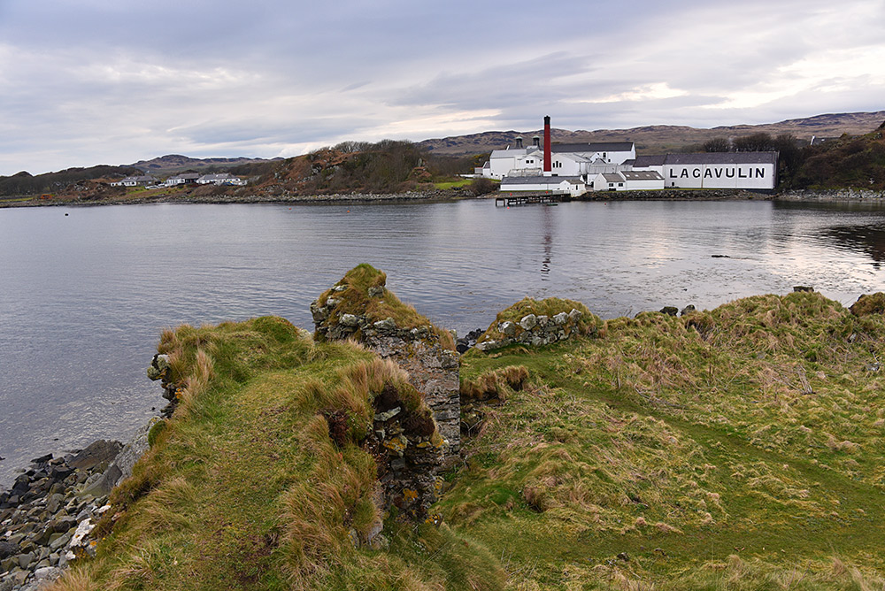 Picture of a view across a bay towards a distillery from the ruined walls of an old castle
