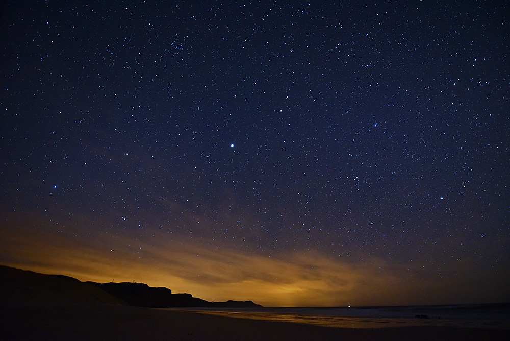 Picture of night sky with thousands of stars of a bay with a beach, some clouds on the horizon