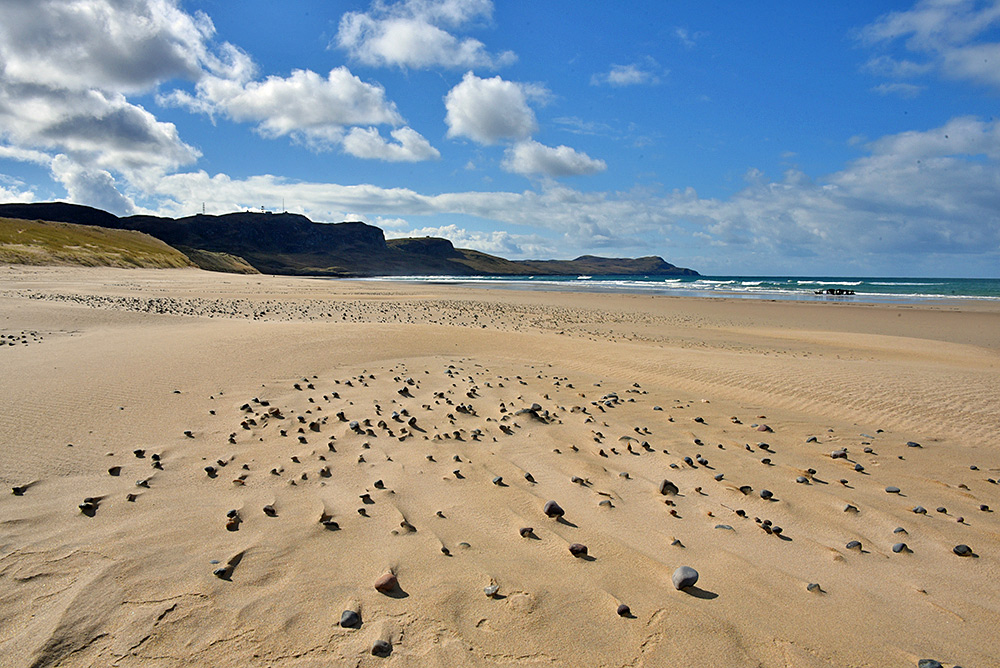 Picture of a sandy beach with a number of small stones/pebbles strewn across the sand