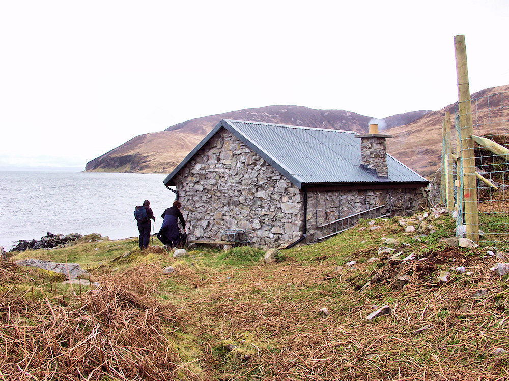 Picture of two walkers arriving at a coastal bothy