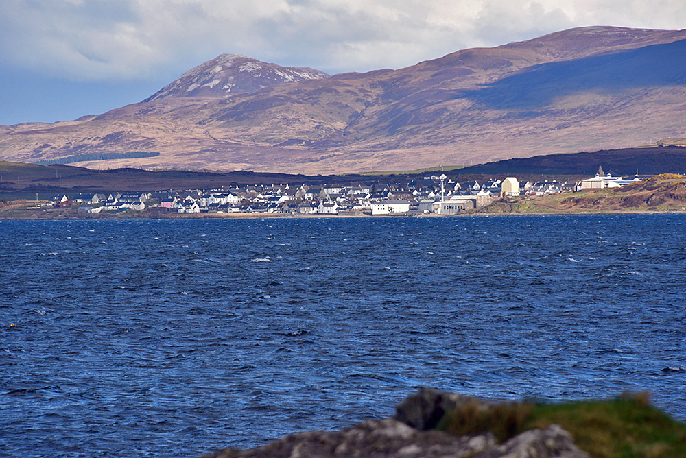 Picture of a coastal village seen across a sea loch, hills in the background