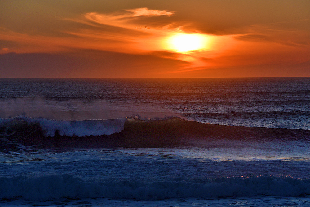 Picture of waves breaking near a shore, the sunset in the background