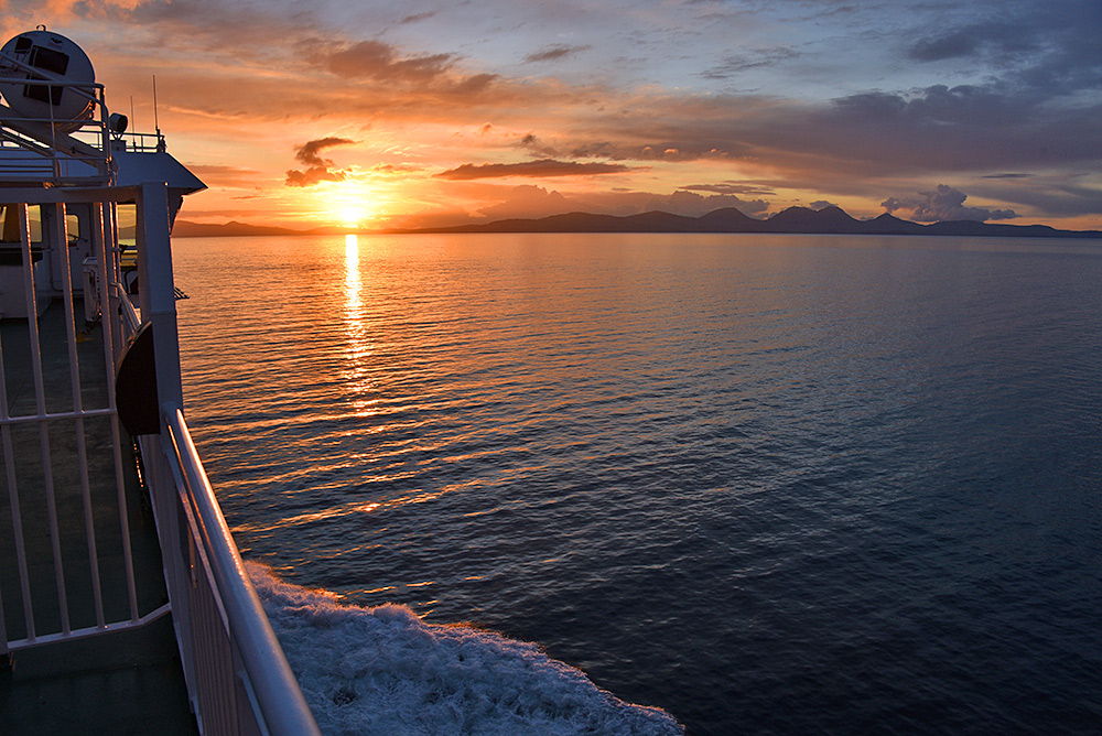 Picture of a view from the deck of a ferry cruising towards a sunset behind an island
