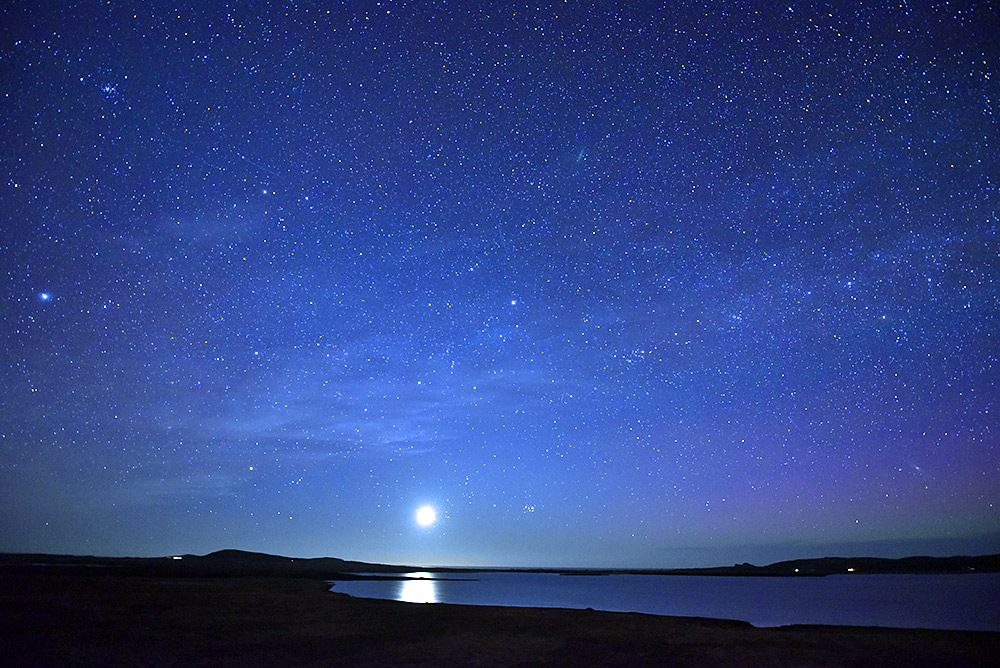 Picture of a loch (lake) at night with a low full Moon and thousands of stars in the night sky