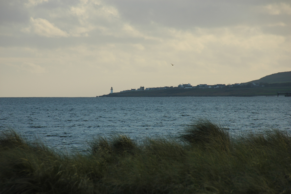 Picture of a coastal village and a lighthouse seen across a sea loch