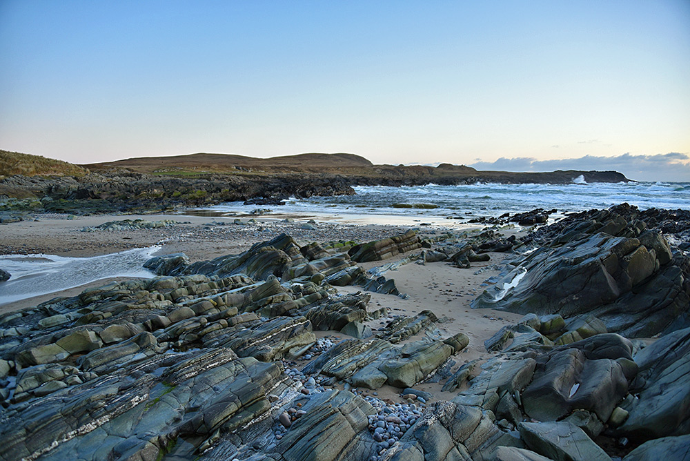 Picture of a beach with exposed rocks and pebbles after storms carried away a lot of the sand