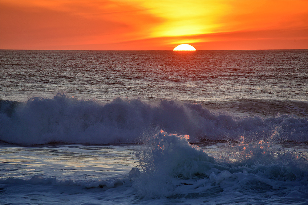 Picture of a wave breaking and splashing with the backdrop of a colourfun sunset