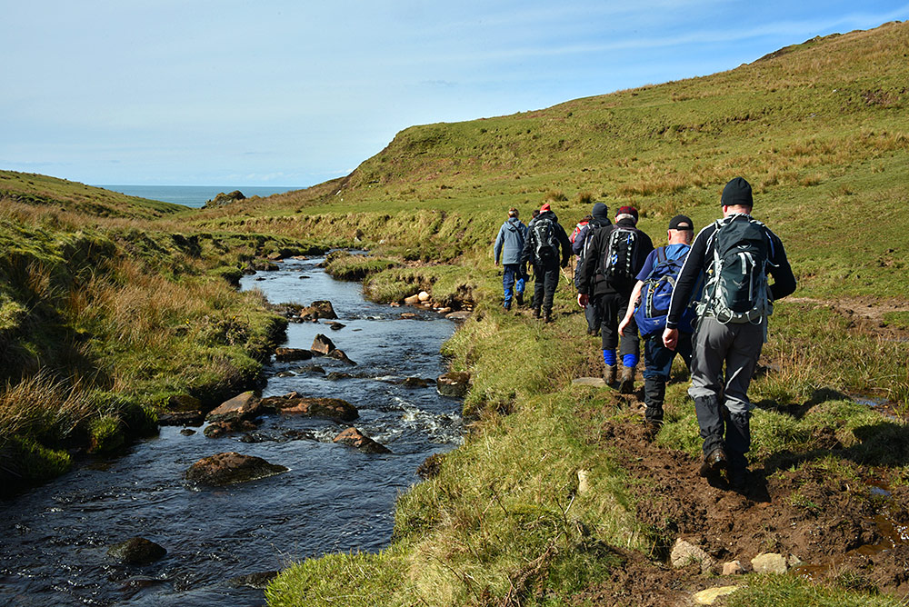 Picture of a group of walkers walking along a stream flowing towards the sea
