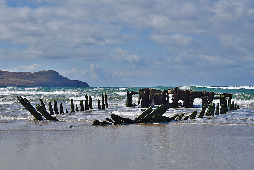 Picture of the remains of a wreck embedded in a beach