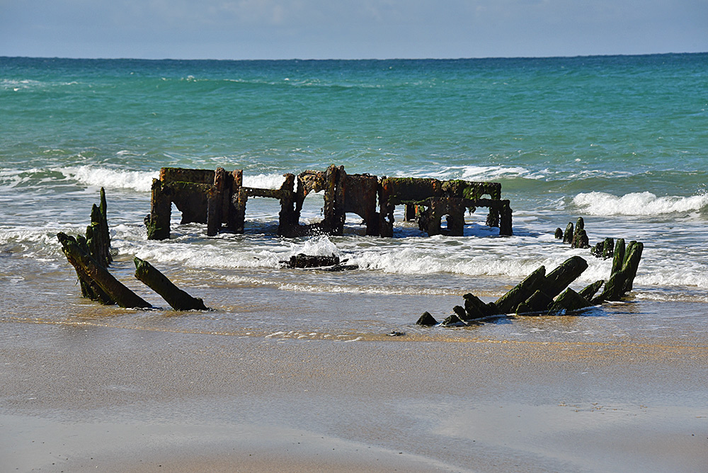Picture of a wreck on a beach, waves washing into the wreck