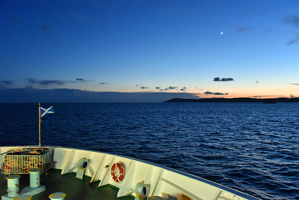 Picture of the bow of a ferry under the last evening light, a crescent Moon in the sky