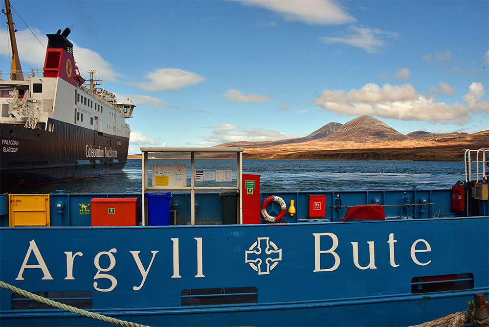 Picture of a view across a sound between two islands, a ferry with Argyll and Bute written on it in the foreground