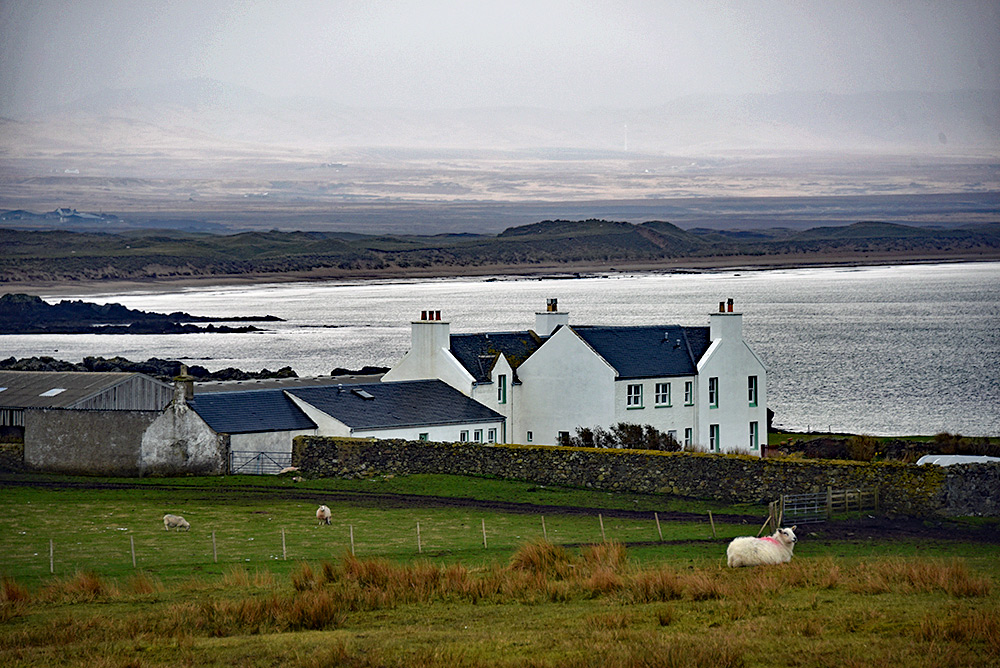 Picture of a remote farm with a bay and beach in the background on a grey and drizzly day