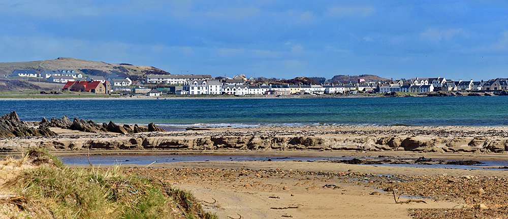 Picture of a coastal village seen from a beach across a bay