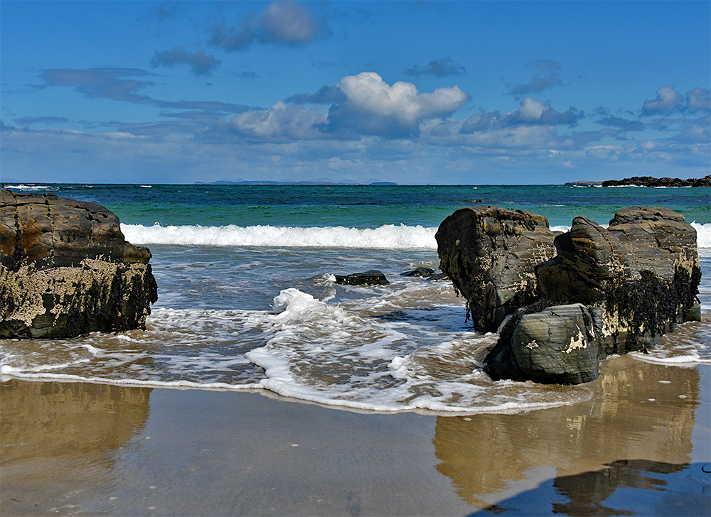 Picture of waves swirling around rocks on a beach on a sunny day