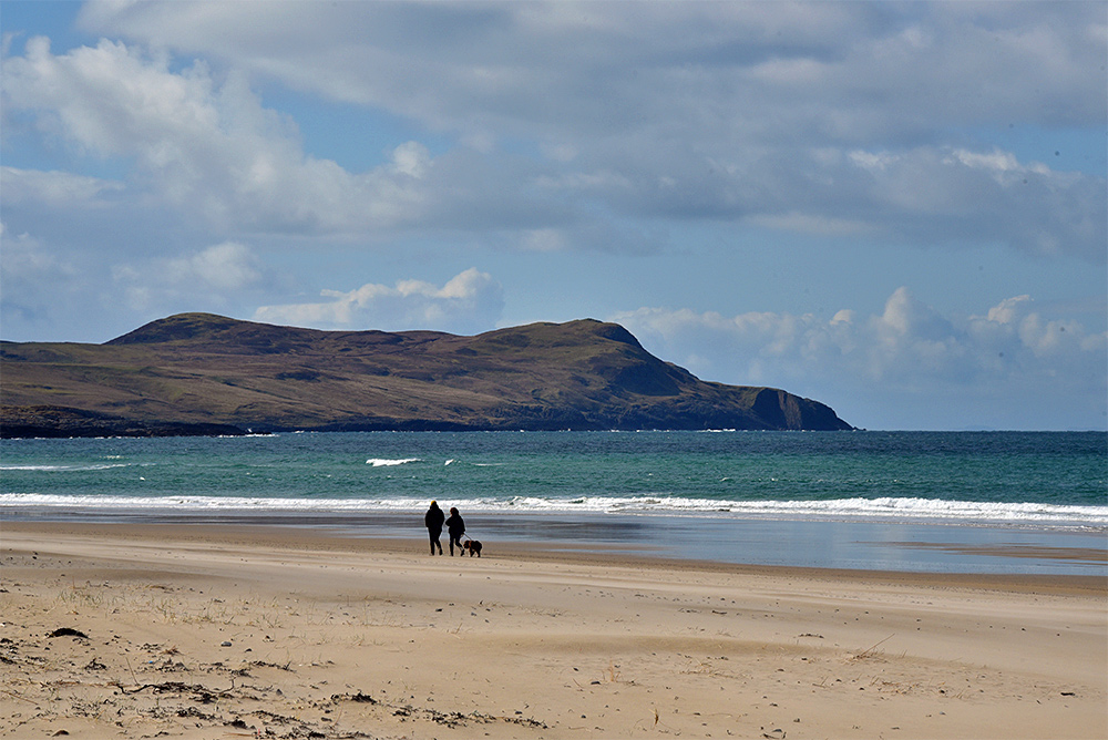 Picture of two people walking a dog on a beach in bay