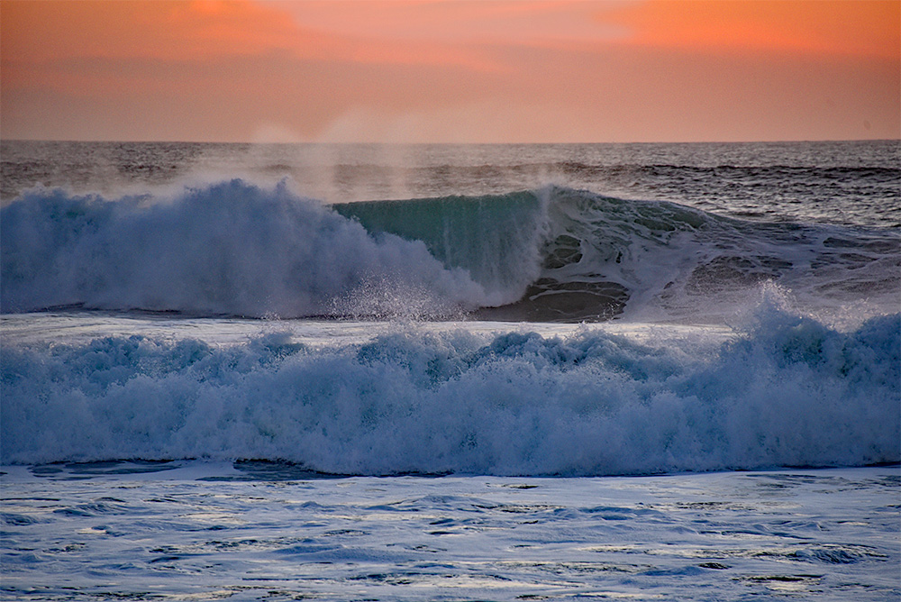 Picture of two breaking waves under a red evening sky