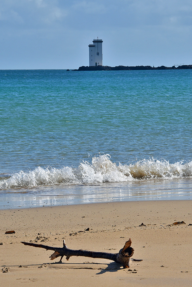 Picture of a square lighthouse seen from a beach