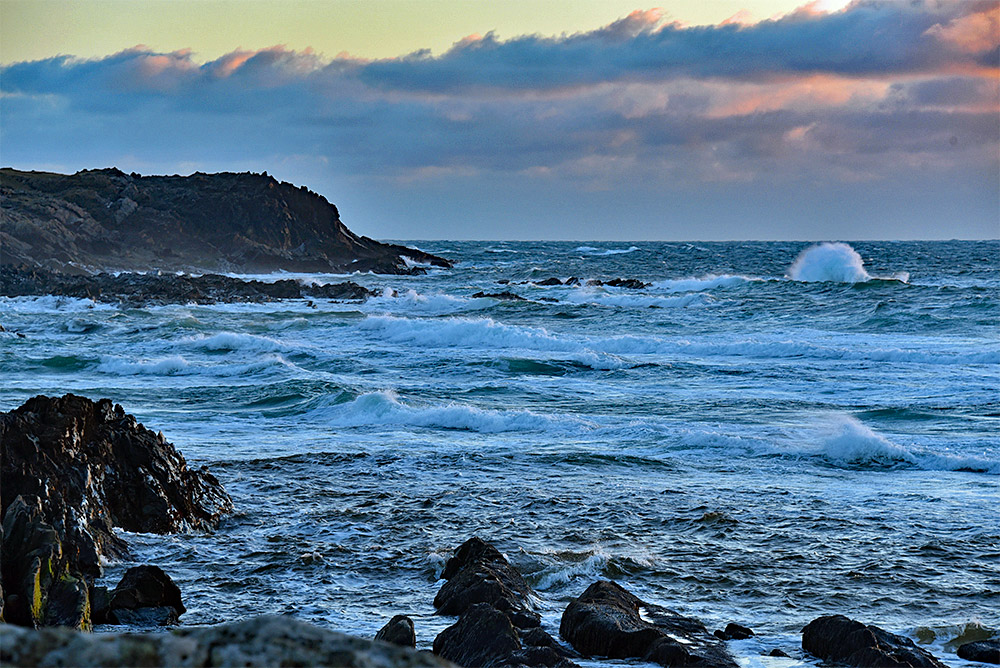 Picture of waves rolling into a bay with a rocky shore
