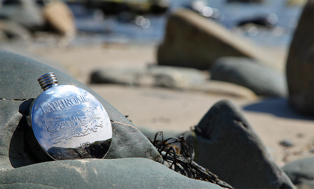 Picture of a Laphroaig hip flask resting on a rock on a beach