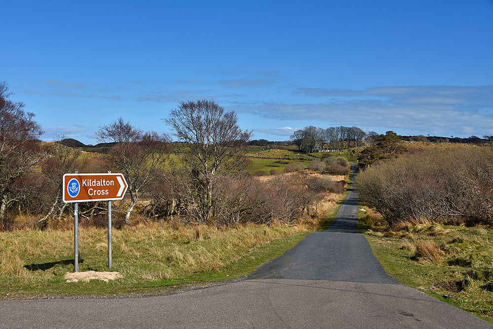 Picture of a road with a sign pointing to the Kildalton Cross