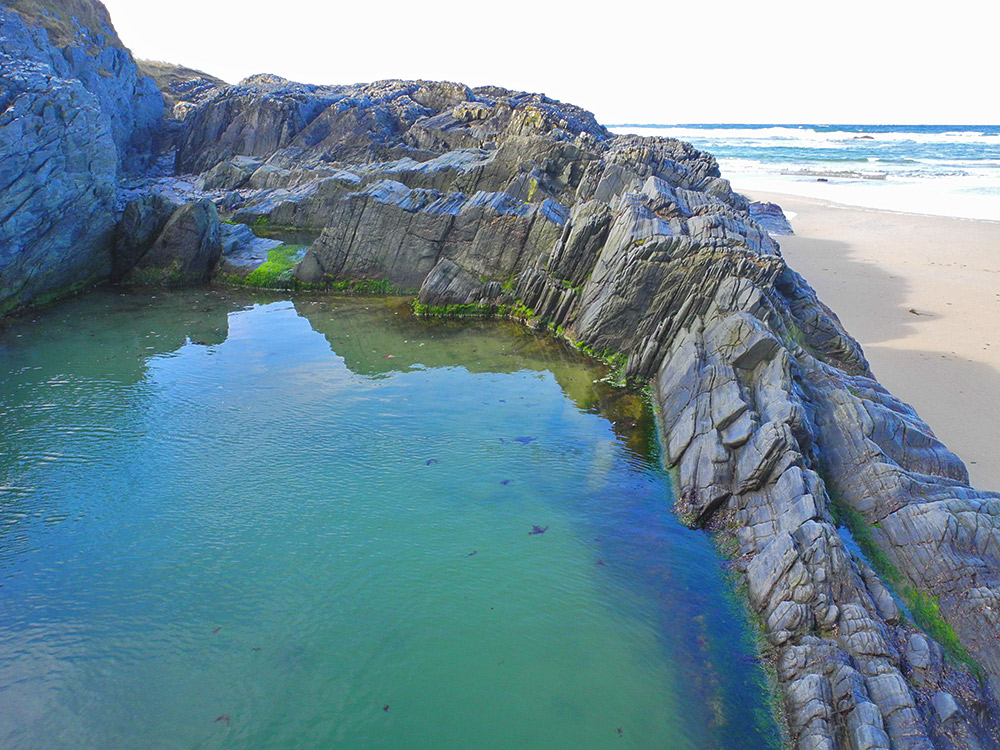 Picture of a large rock pool next to a beach
