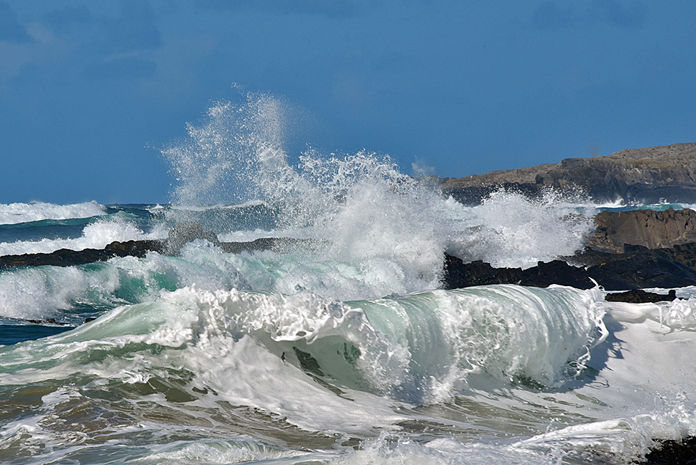 Picture of rolling and breaking waves as they reach a rocky shore