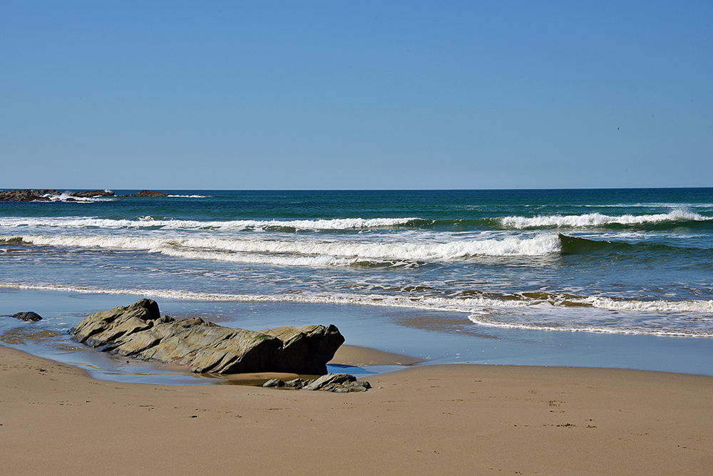 Picture of a beach with a few rocks, some small waves rolling in