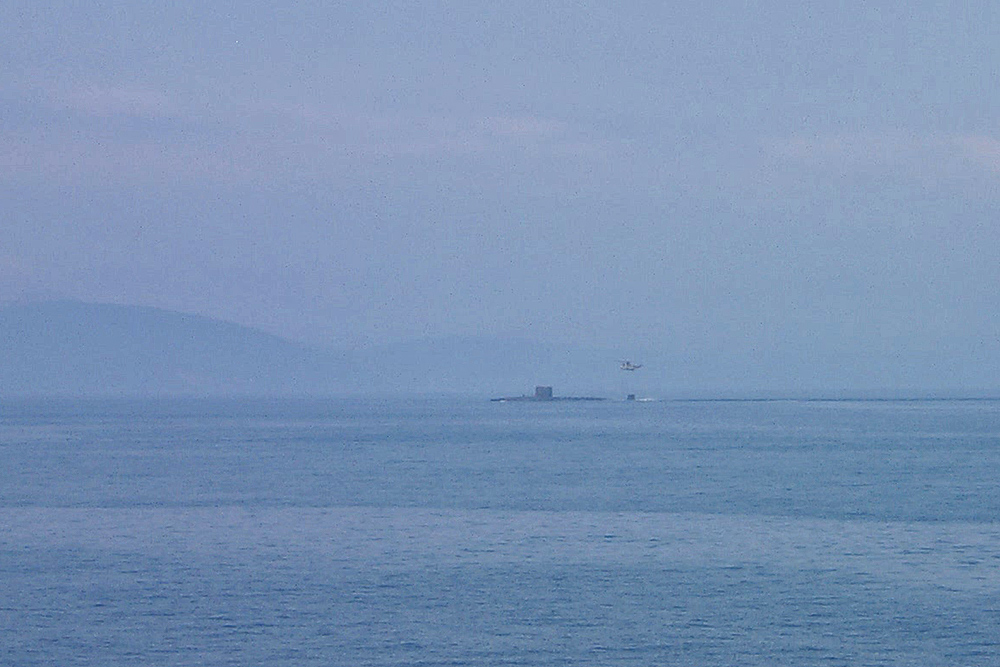 Picture of a submarine with a helicopter hovering above, taken from a distance
