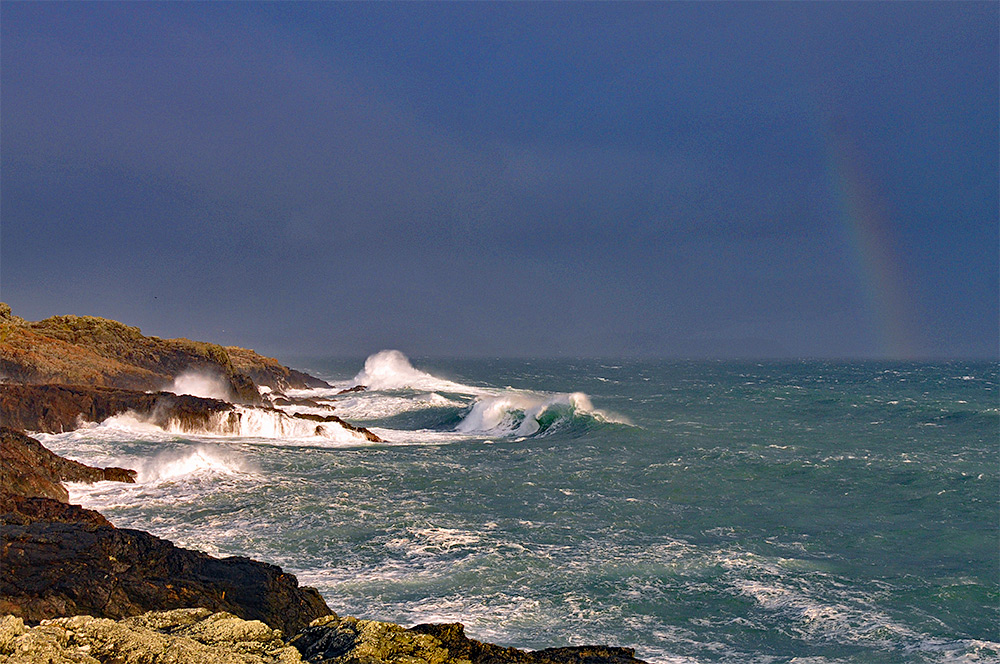 Picture of waves breaking over rocks, a rainbow in the distance