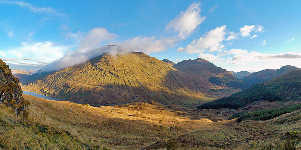 Panoramic picture of a road through two glens (valleys) over a mountain pass