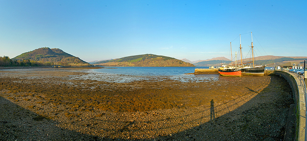 Panoramic view of a sea loch at low tide, two ships sitting on the sea floor