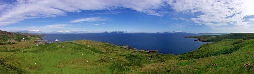Panoramic picture of a view from a hill on a small island over the shore, the sea and neighbouring islands