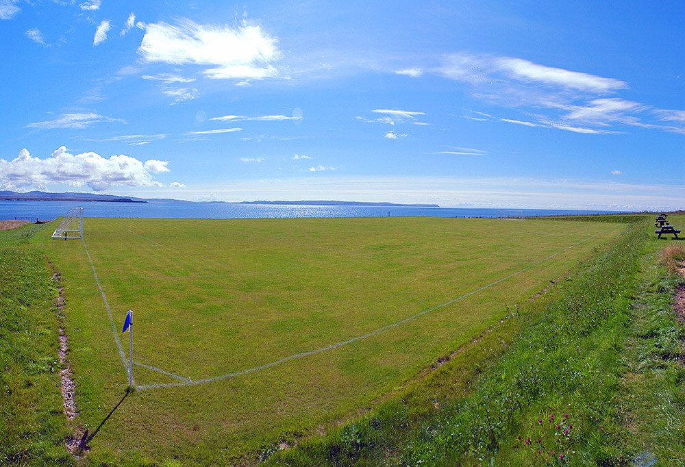 Picture of a football pitch next to a sea loch