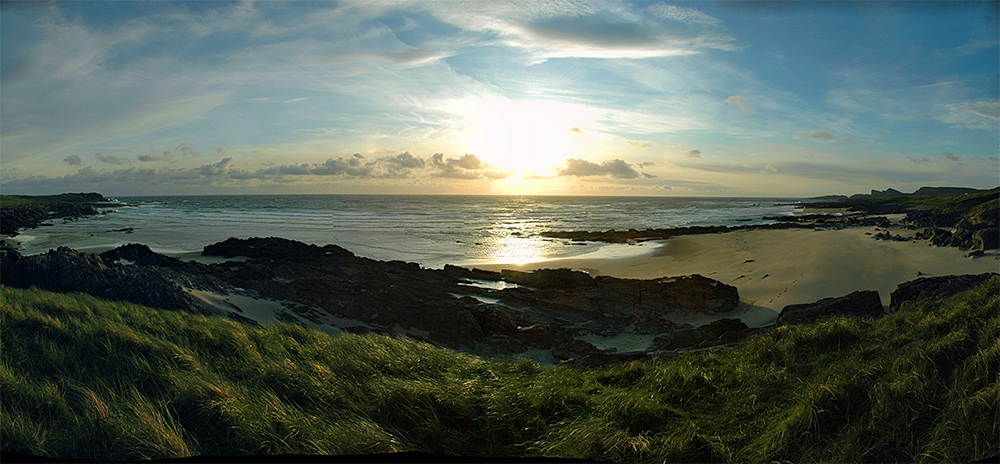 Panoramic picture of a bay with a beach and rocks in the evening with sunset approaching