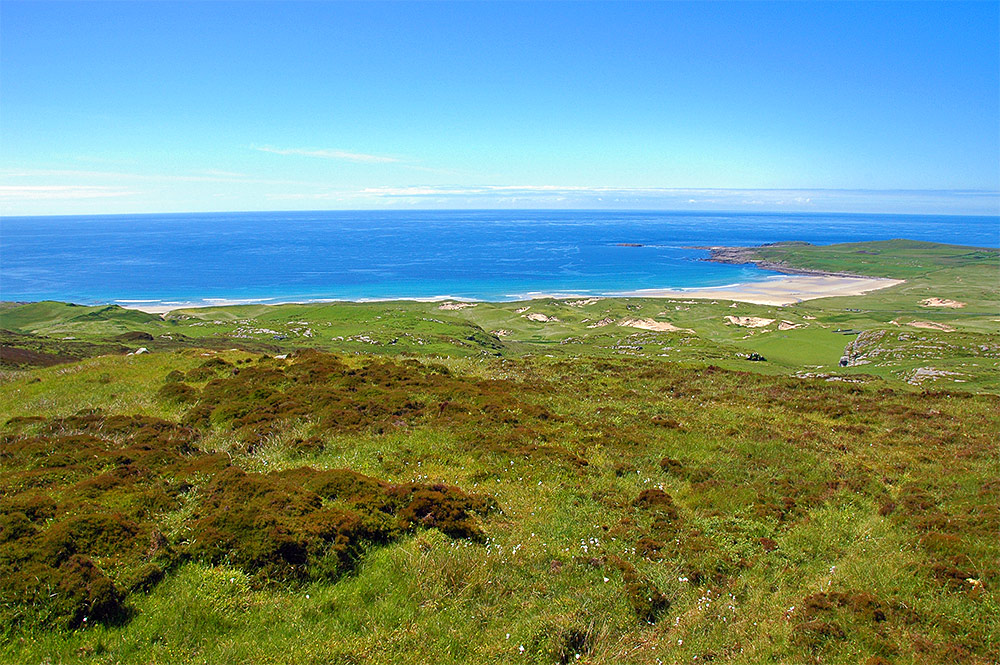 Picture of a bay with a sandy beach seen from the top of a hill above the bay