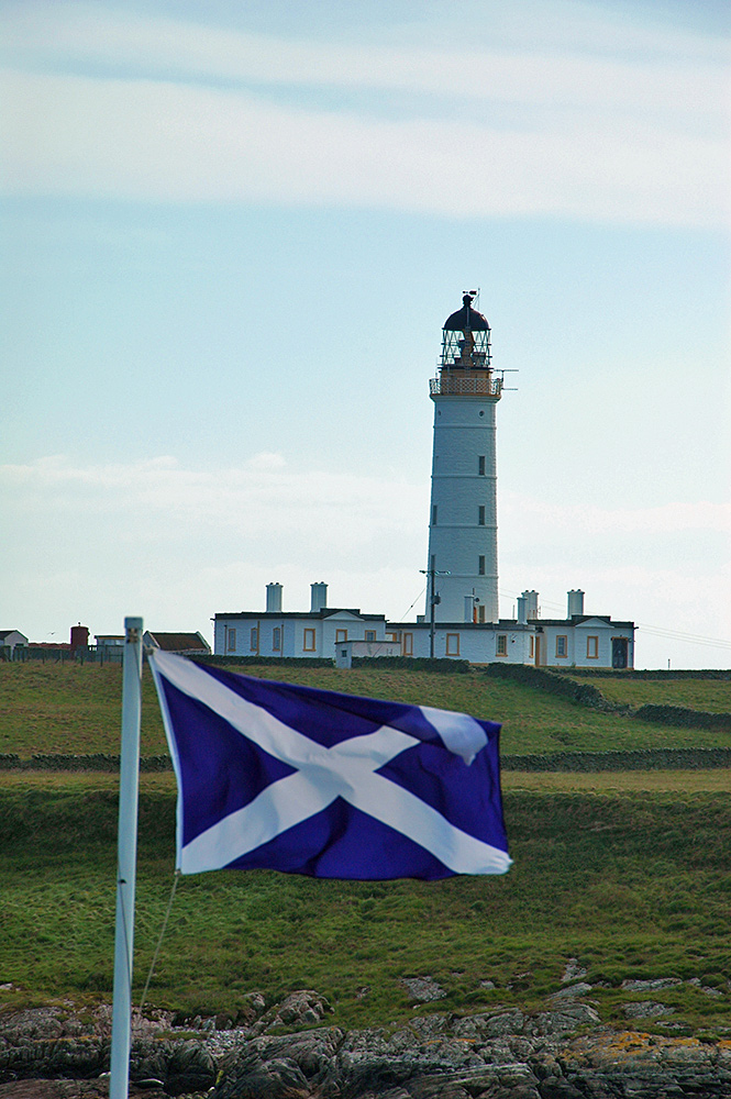 Picture of a lighthouse with the Saltire (Scottish national flag) flying in front of it