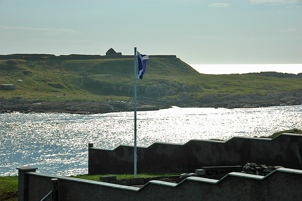 Picture of a Saltire flying in a coastal garden, an island opposite