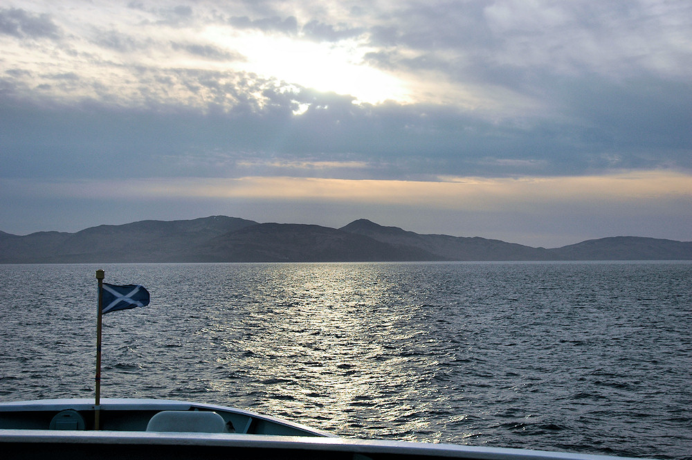 Picture of a ferry approaching a sound between two islands, some sunshine above but mostly covered in clouds