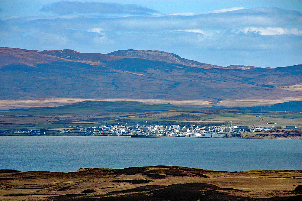 Picture of a coastal village with a distillery seen across a sea loch