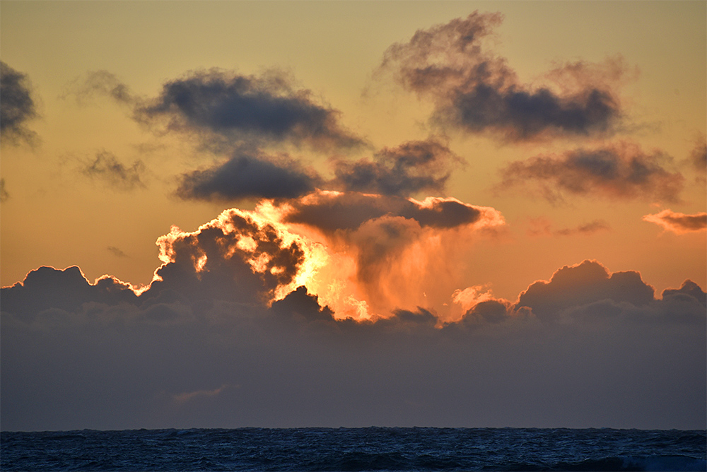 Picture of colourful and interestingly shaped clouds during a sunset over the Atlantic
