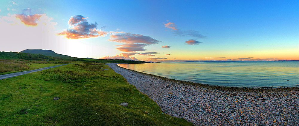 Panoramic picture of a view over a bay with a pebble beach in the gloaming