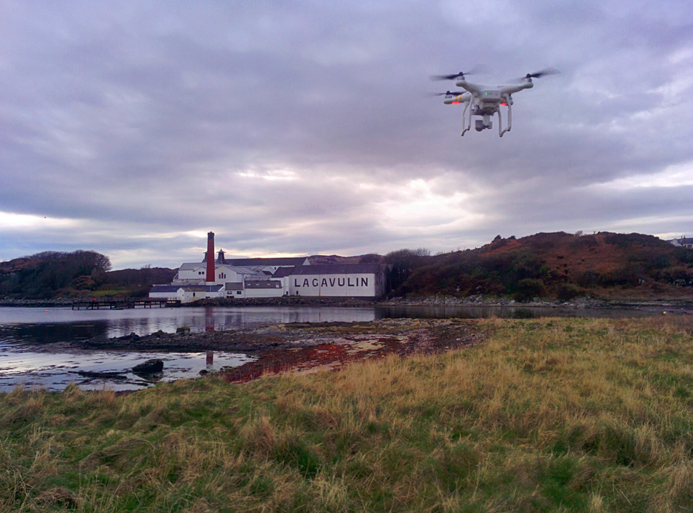 Picture of a drone hovering in the air near a bay with a distillery on the other side