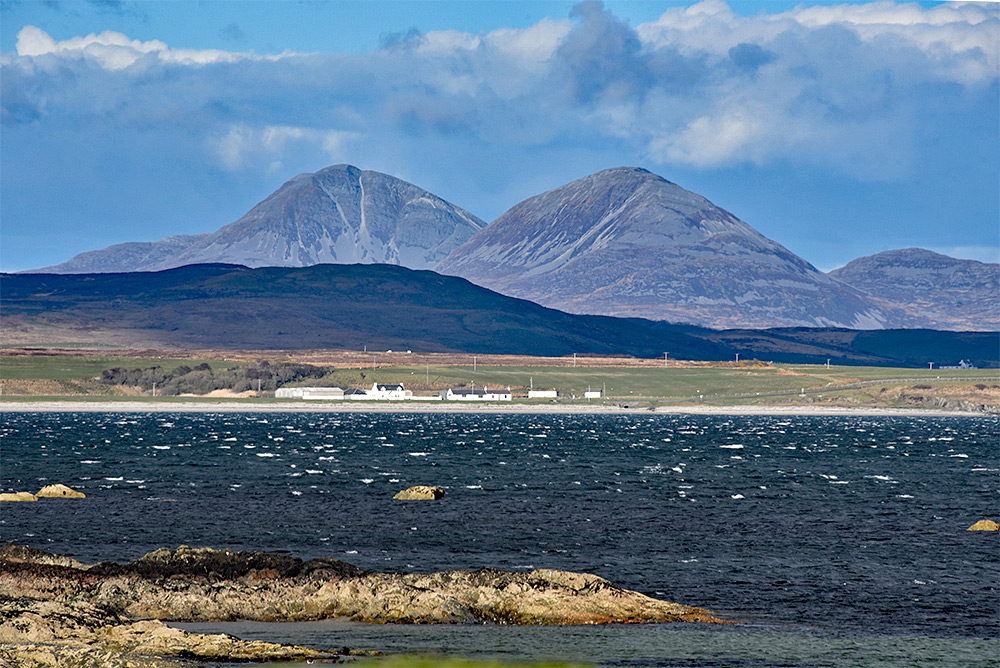 Picture of two mountains towering over a farm at a sea loch