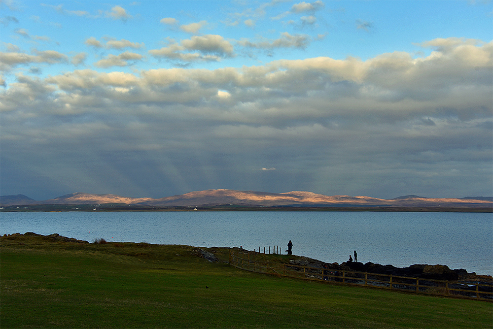 Picture of a calm evening at a sea loch, some people on rocks near the shore. Strange light rays on the horizon