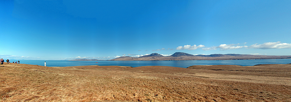 Panoramic picture of a view over a sound between two islands, mountains visible on the other island