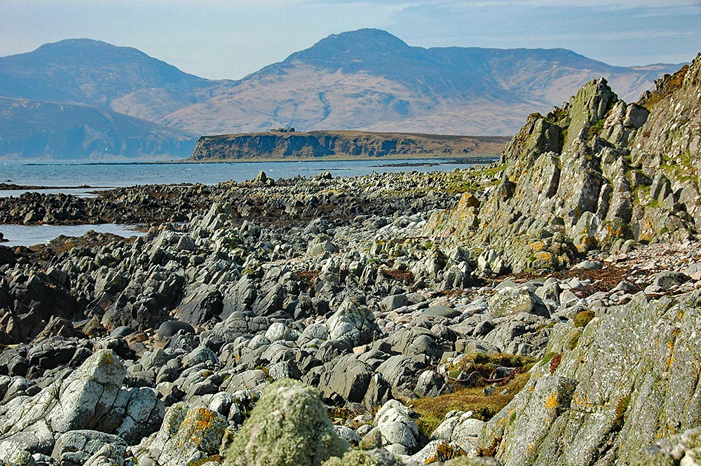 Picture of a ragged rocky shore, a small island with a castle ruin in the background