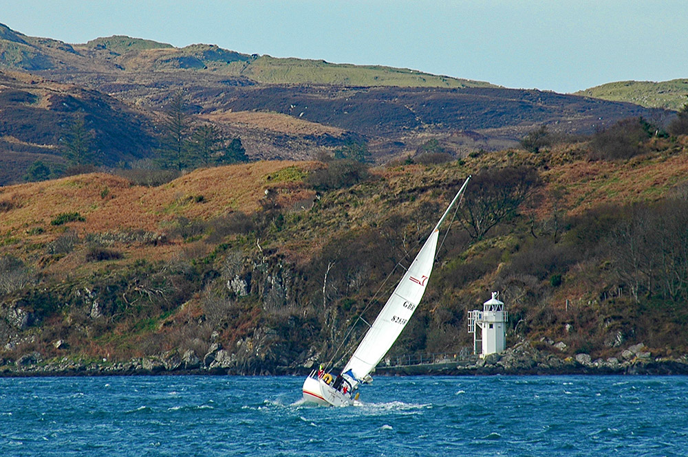 Picture of a sailing yacht tacking upwind in strong winds near a small lighthouse